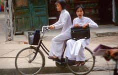 Girls in traditional Ao Dai on bicycle