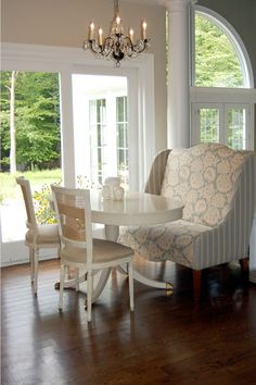 dining rooms - wing chair breakfast room Wingback settee, white pedestal table and crystal chandelier.