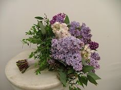 Lavender, purple, light pink, and white Lilacs accented with assorted types of Eucalyptus, and finished off with a soft, sheer white ribbon wrap.