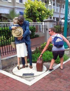 Estatuas abrazándose y un chico simula robar su maleta