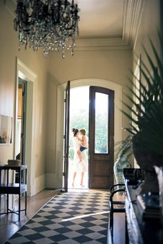 Sara and Ruffy barefoot at the entryway decorated with a painted runner and a chandelier that came with the house.