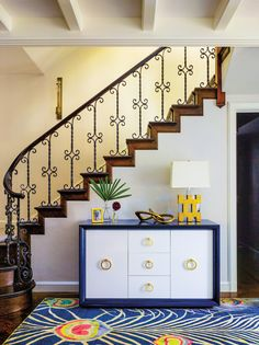Weiss and Barnett incorporated some of the home's original details, such as a grillwork banister, which frames a custom-made Modernist credenza in the entry foyer.