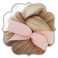 A pink bow nestled inside a cute braided blonde bun.