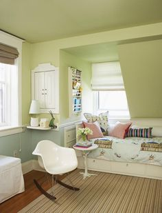 This shared bedroom in gender-neutral hues includes clever nooks under the eaves.    Storybooks are stored above the bed instead of on a bulky bookshelf, and built-in drawers and a cupboard maximize storage in an awkward corner. An Eames molded plastic rocker works with Ikea staples to create a playful look.