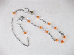 Chunky orange necklace with orange, and clear beads, multi colored orange grey and black beads, with large silver hoops, on chunky silver chain with lobster clasp. This orange necklace is about 36 inches long. ***SEE ALL THE NECKLACES IN MY SHOP AT: https://www.etsy.com/shop/RalstonOriginals?section_id=10816830&ref=shopsection_leftnav_1  See all the jewelry in my Etsy Shop at https://www.etsy.com/shop/ralstonoriginals?view_type=gallery. I have many more long necklaces in many colors and…