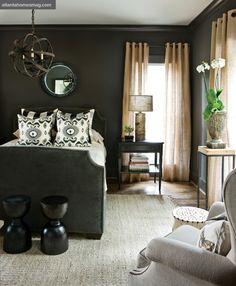 The dark gray of the guest bedroom is tempered by light surfaces elsewhere: camel-colored burlap curtains, a braided jute rug, pale accent tables and a birch bark lamp.