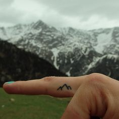 This sweet tiny tattoo of mountains is a good reminder to all of us to get outside and have some fun.