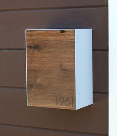 This is a Stainless Steel and Walnut mailbox measuring 9W x12.5H x 6D. I designed this mailbox after the 1950s black mailbox that used to hang on my house. I really liked the way it functioned and it inspire me to design this modern version of it. The wood gives it some warmth while the 14ga Stainless Steel cover protects and creates a sturdy shell. It easily attaches to an exterior wall by two keyhole brackets located on the back of the mailbox. These brackets hang from two round head…