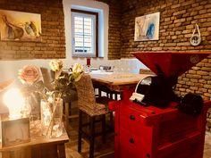 Das Weinstüberl im abendlichen Glanz. Tisch aus alter Maschine und Holzbrettern.