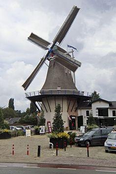 Molen De Koe met rechts daarvan het Pakhuis. Eind jaren 80 is de molen door blikseminslag afgebrand. Door het opzetten van een stichting en veel inzet is de molen herbouwt en neemt hij een markante positie in.