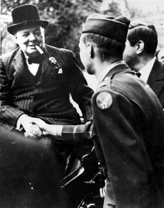 Winston Churchill, British statesman, World War II, 1939-1945. Churchill (1874-1965), Britain's wartime Prime Minister, smiling and smoking a cigar, shakes hands with a soldier. (Photo by Ann Ronan Pictures/Print Collector/Getty Images)