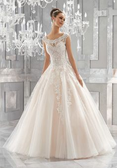 A Fairytale Ballgown is Brought to Life with Crystal Beaded, Embroidered Lace Appliqués and a Full Tulle Skirt. An Elegant Off-the-Shoulder Neckline and Intricate Illusion Back Complete the Look. Colors Available: White, Ivory, Ivory/Light Gold,Ivory/Blush.