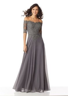 This MGNY by Mori Lee 71822 charcoal formal dress features a beaded lace bodice with a scalloped off-the-shoulder neckline and illusion half sleeves. This A-line gown is fashioned in stretch mesh, finished with a slim belt. Mother Of The Bride Dresses Long, Mother Of Bride Outfits, Mothers Dresses, Long Mothers Dress, Brides Mom Dress, Mob Dresses, Bridesmaid Dresses, Wedding Dresses, Lace Wedding