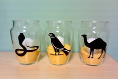 For an Egyptian themed party, print out animal images and cut them out. Glue them onto vases. Fill the vases with sand and place simple candles inside them.