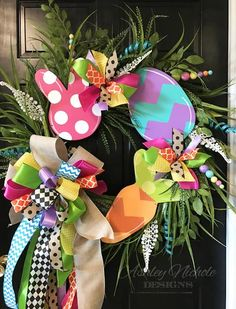 """Such a large beautiful Easter wreath! Our Large Easter Assortment Grass Wreath features three hand painted wooden pieces, a bunny, egg, and carrot. The wreath is made with an assortment of grasses, glittery picks and is adorned with three beautiful bows. You can request the items or bows to be different colors in the custom text box above, IF none is listed then you will receive the wreath as pictured.          This wreath is built on a 24"""" round grapevine.                            ..."""