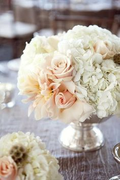 Compote inspiration | Tables will feature a lush gold compote filled with white hydrangea, ivory garden roses, blush Candy Bianca roses, white freesia, ivory spray roses and light pink dahlias surrounded by clear votive candles.