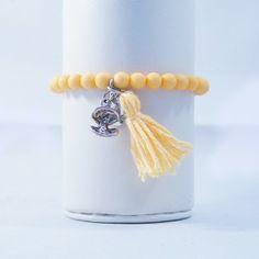 Geel armbandje met mooi bedeltje gemaakt van acrylkralen.