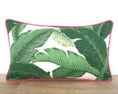 This tropical pillow cover comes in an indoor/outdoor fabric and is water and stain resistant. Colors include teal, green, turquoise and cream and goes perfect with brown outdoor furniture. Ive added a piping in hot pink for some pop. The inner seams are serged for durability and the invisible zipper is hidden on the bottom . Front and back of the outdoor pillow features the same fabric .  Features of the banana leaf pillow cover:  Size: oblong pillow cover  Material: 100 % Polyester, in...
