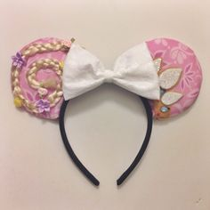 These handmade mouse ears are perfect for displaying your love for Rapunzel! They feature her lovely braided hair compete with flowers on one ear, and
