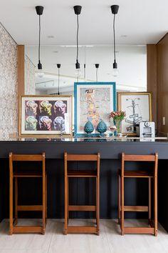 Decoração de apartamento  com banquetas de madeira, parede com espelho, quadros e adornos.