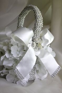 flower girl basket with brooches, white hydrangea petals, satin bows and bling via Etsy