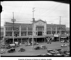 Colman Dock, ca. 1934. For many years, travellers went to Seattle's Colman Dock at the foot of Marion Street to catch ferries to Bremerton, Port Angeles, or other towns on Puget Sound. The dock building housed the ferry offices and a marine supply company. Ye Olde Curiosity Shop is just behind the whale ribs and totem pole on the ground floor. Colman Dock and the Curiosity Shop still stand on Seattle's waterfront, although the buildings have changed.