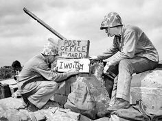 Original Description: Hell's island gets letters from heaven. Marines of the Fourth Division receive airmail in the most literal sense of the word when planes flew over Iwo and parachuted mail bags to the beach. The post office was in operation on the tenth day of the campaign. Setting up the sign post are (left to right), Sergeant B.D. Boyant, of Spartansburg, PA. and Corporal Kenneth E. Hales of Pasco, Washington.