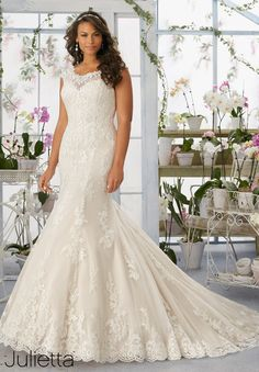 Alencon lace appliques and scalloped edging frosted with beading on net gown over soft satin.