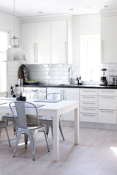 Simple white modern kitchen with large drawer pulls, subway tile splash back, black countertop, eclectic dining table and chairs. Kitchen Dinning Room, Dining Area, Dining Rooms, Dining Table, My Home Design, House Design, Nordic Kitchen, Design Furniture, Kitchen Interior