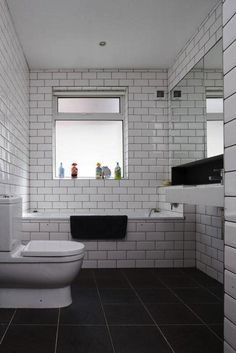 Tiled bath with white tiles and dark grout