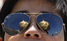 23. Februar 2014: Der #Goldene #Fels, eine der heiligsten buddhistischen Stätten in #Myanmar, spiegelt sich in der Brille eines Besuchers. (Foto: Reuters)