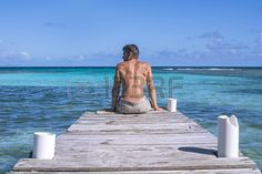 Muscular shirtless Caucasian man sits on edge of dock over beautiful blue green tropical waters of Playa Larga on the Caribbean island of Isla Culebra in Puerto Rico
