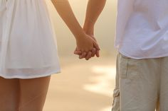 Close up of a couple walking and holding hands on the beach.jpg by…