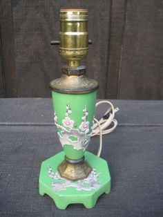 "Vintage Moriage Boudoir Lamp in Green circa 1940s.  This beautiful lamp features a raised design of cherry blossoms and tooled brass accents. It would make a lovely nightstand or dresser lamp. Measures 9.5"" tall x 4.75"" in diameter. $125 - Cabootle"