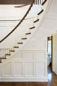 Traditional curved staircase boasts white wood spindles and a dark stained railing on wall accented with wainscoting as well as an under staircase hallway.
