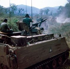 M-113 APC's lay down supporting fire as they advance against NVA forces in South Vietnam.