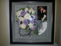 preserved small cascade bouquet framed with 4x6 picture, boutonniere, garter, and braided rope in a black shadow box with grey suede mat.