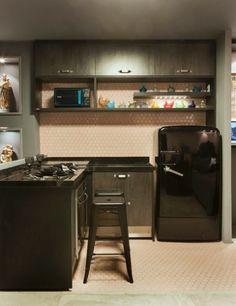 """Neste apê dúplex, a copa e a cozinha tiram partido do contraste de tons e estilos. O rosa """"antigo"""" das pastilhas no piso e parede sobressai ao cinza e ao preto dos eletrodomésticos e mobiliário."""