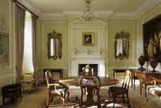 sun-lit dining room with 18th c. table & chairs, and two-tier chimney piece set at Georgian era Peckover House, in Cambridgeshire, England
