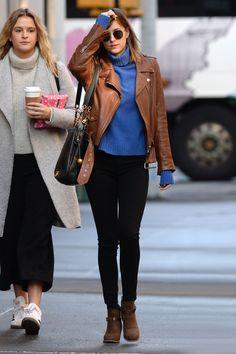 Dakota Johnson in a blue cardigan, cognac moto jacket, skinny black pants, and brown ankle boots.