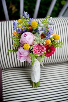 Bright mixed bridal bouquet of peonies, garden roses, poppies, delphinium, craspedia and Queen Anne's lace.