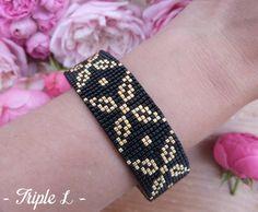 ~ DESCRIPTIF ~ Ce bracelet manchette LAVINIA est composé dun tissage fait main avec des perles de verre Miyuki et dune manchette en laiton. Couleurs des perles : noir - doré. Dimensions : 2 cm de large.  Voir dans la boutique pour les autres bijoux de la parure LAVINIA : - une bague - une paire de boucles doreilles - un pendentif - trois autres bracelets  ~ MATERIEL UTILISE ~ - Perles de verre japonaises Miyuki - Manchette en laiton brut puis verni par mes soins  ~ ENVOI ~ Les bijoux sont…