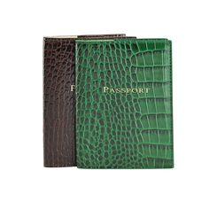 This Crocodile Embossed Leather passport case makes the perfect travel companion. Fits neatly in purse or pocket, this slim leather jacket features left and right pockets specifically for your passport, customs card or baggage claim ticket.