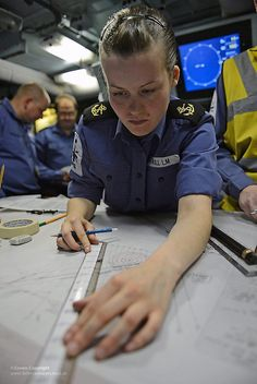 A Royal Navy sailor plots a course on a navigational chart onboard Type 23 frigate HMS Northumberland.