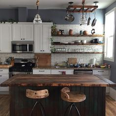 Rustic kitchen. The grey paint is balanced against the dark wood and white shaker style cabinets.