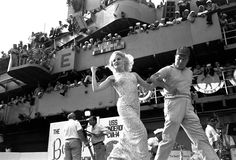 Actress Carroll Baker snaps her fingers at sailors cheering from the bridge of aircraft carrier USS Ticonderoga as Bob Hope leads her across a stage set up on the flight deck. More than 2,500 sailors saw the Hope troupe's show on the carrier off the coast of Vietnam on December 27, 1965.