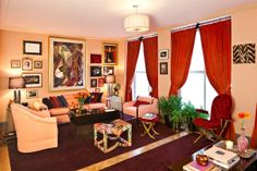 Living room that Zac Posen and Morris Adjmi collaborated on with Parquet wood floor, purple area rugs, large windows with orange curtains, peach walls, armchairs and sofa, a dark coffee table, a tufted red velvet seat with matching ottoman