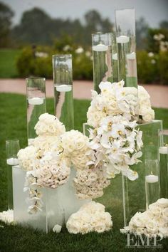 So pretty! All white flowers with tall vases and floating candles <3