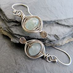 An icy faceted genuine Aquamarine rondelle is embraced by sterling silver woven wire