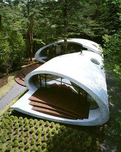 The Shell Residence by ARTechnic is located just outside of Tokyo in Karuizawa, Japan. The house is surrounded by conifer forests and the structure itself was constructed around an ancient Fir tree. The residence was built using long-lasting concrete which, along with an automated centralized system, aids in energy efficiency and serves to protect the home from the forest's humidity and cold weather.